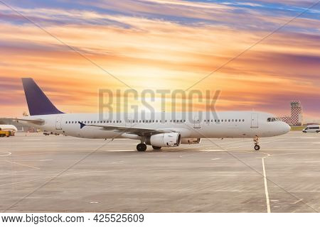 Passenger Airplane On Runway Near The Terminal In An Airport At Sunset Time