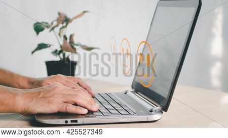 A Man Use Laptop And Choose Face Smile Emoticon Show On Virtual Screen. Survey, Poll Or Questionnair