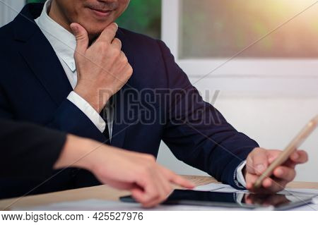Image Of A Young Businessman Using Touchpad At The Meeting With His Colleague. The Concept Is To Rep