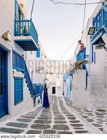 Mykonos Greece, Young Man And Woman In Dress At The Streets Of Old Town Mikonos During A Vacation In
