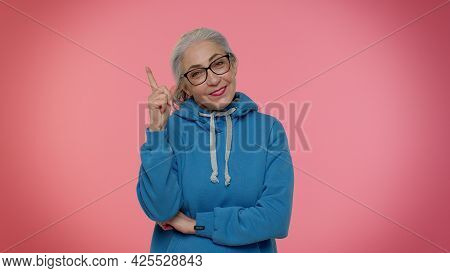 Inspired Mature Old Gray-haired Granny Woman In Casual Blue Hoodie Pointing Finger Up With Open Mout