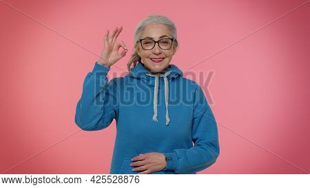 Mature Old Gray-haired Granny Woman Looking Approvingly At Camera Showing Ok Gesture, Like Sign Posi