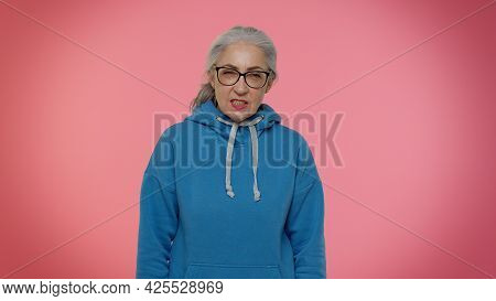 Upset Tired Sad Senior Old Grandmother Woman In Blue Hoodie And Glasses Looking At Camera With Bored