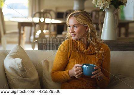 Happy caucasian woman sitting on couch in living room holding coffee cup, smiling and looking away. spending free time at home.