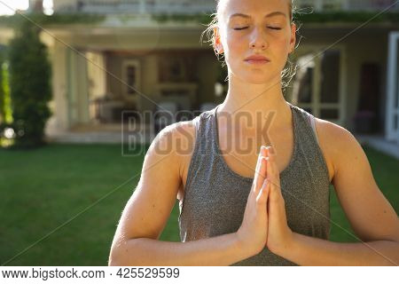 Tranquil caucasian woman practicing yoga in sunny garden, meditating with eyes closed. health, fitness and wellbeing, spending quality time at home.
