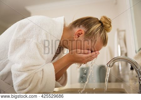 Caucasian woman in bathroom wearing bathrobe, standing at basin washing face. health, beauty and wellbeing, spending quality time at home.