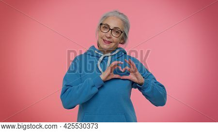Smiling Elderly Granny Gray-haired Woman In Makes Heart Gesture Demonstrates Love Sign Expresses Goo