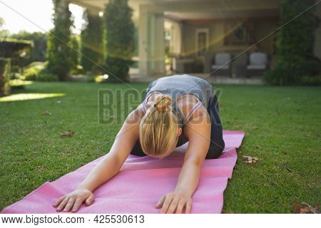 Caucasian woman practicing yoga in garden, kneeling and stretching. health, fitness and wellbeing, spending quality time at home.