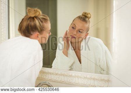 Caucasian woman in bathroom wearing bathrobe, looking in mirror and moisturising face. health, beauty and wellbeing, spending quality time at home.