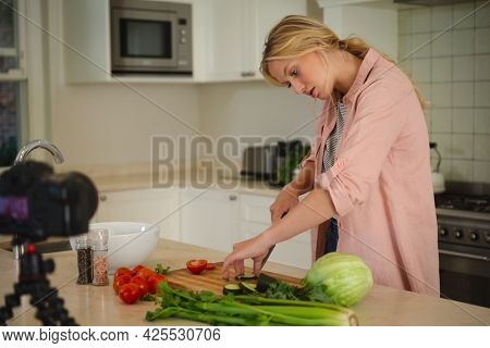 Caucasian woman in kitchen chopping vegetables and using camera, making cooking vlog. technology and communication, cookery vlogger at home.