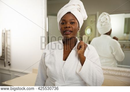 Portrait of happy african american woman in bathroom wearing bathrobe, with towel on head. health, beauty and wellbeing, spending quality time at home.
