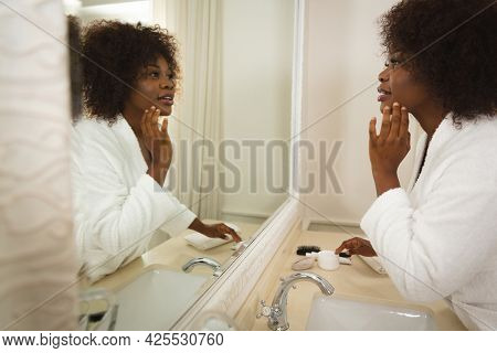 Happy african american woman in bathroom wearing bathrobe, looking in mirror and moisturising face. health, beauty and wellbeing, spending quality time at home.