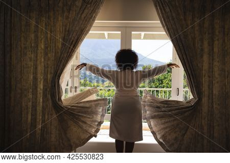 African american woman standing in front of window with sunny mountain view drawing curtains. spending free time at home.