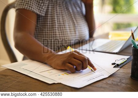 Midsection of african american woman working in living room using laptop and making notes. technology and communication, flexible working from home.
