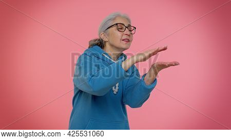 Mature Old Granny Woman In Casual Blue Hoodie Showing Gesture Of Wasting Or Throwing Money Around Ha