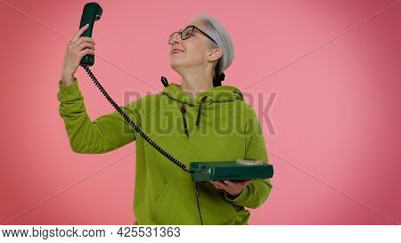 Crazy Elderly Granny Gray-haired Woman In Casual Green Hoodie Talking On Wired Vintage Telephone Of