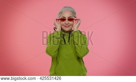 Portrait Of Seductive Senior Old Granny Gray-haired Woman Wearing Sunglasses, Charming Smile. Posing
