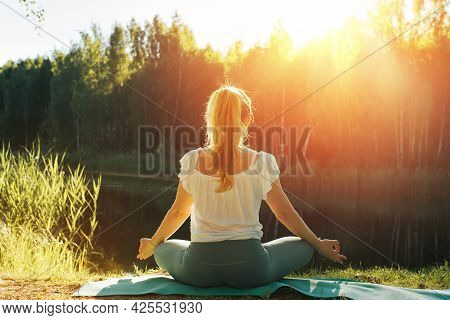 Meditation Outdoors During A Beautiful Sunrise Or Sunset. Fitness Young Woman Meditating In Lotus Po
