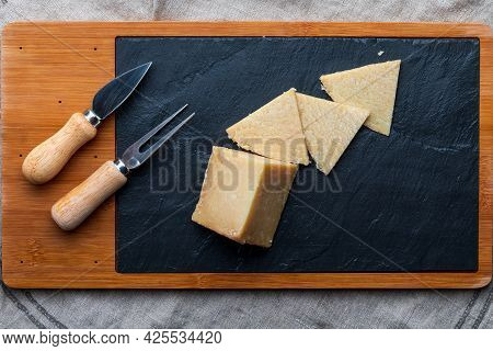 Cured Sheep Cheese. Cut Into Pieces On Wooden Board And Black Slate. Fork And Knife For Cheese. Top