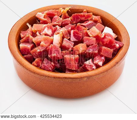 Iberian Ham (serrano) Cut Into Cubes (diced). In Clay Bowl. Isolated On White Background.