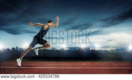 One Professional Male Runner, Jogger Training At Stadium In Evening. Caucasian Fit Athlete Practicin
