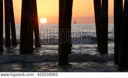 Waves Splashing Under Pier, Sunset In Oceanside, California Usa. Ocean Water, Sun And Wooden Piles.