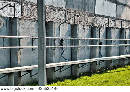 A Concrete Wall With Barbed Wire At The Top. Special Zone. Strictly Protected Object. Prison Or Plac