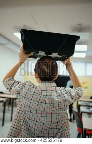 Smiling School Boy Walking While Holding A Box With Plastic Robotic Peaces On His Head Entering In T