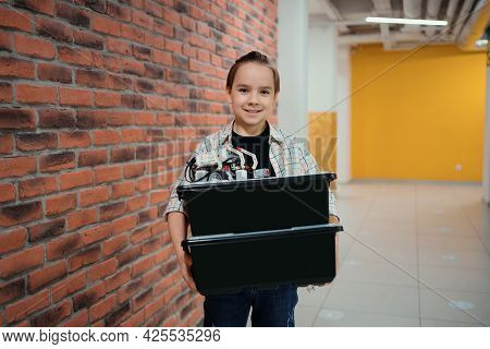 Smiling School Boy Walking While Holding Boxes With Plastic Robotic Peaces On Brick Wall Background.