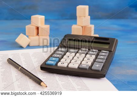 Office Supplies - Calculator, Eyeglasses, Pen And Document Lie On The Wooden Table. High Quality Pho