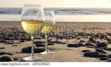 Two Wineglasses On Sandy Ocean Beach. Couple Of Glasses And Pebbles, White Wine For Romantic Date Ne