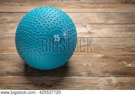 heavy rubber slam ball filled with sand on a rustic wooden deck, exercise and fitness concept