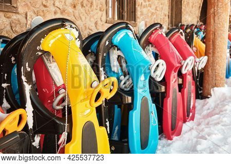Row Of Colorful Sleds To Rent At Ski Resort. Snow Sleighs. Winter Leisure Activities