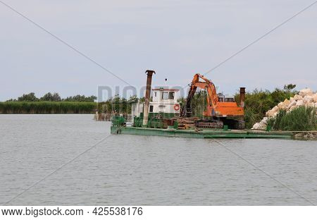 Bulldozer On The Platform On The River In The Construction Site