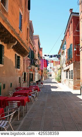Tables And Chairs Of An Alfresco Bar On The Island Of Venice Without People During Lockdown
