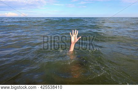 Hand Of The Person In Distress Who Is About To Drown In The Middle Of The Sea