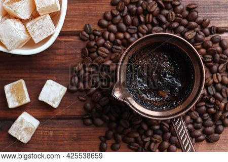 Turkish Coffee With Turkish Delight In Cezve On A Wooden Table Close-up With Coffee Beans. Top View,