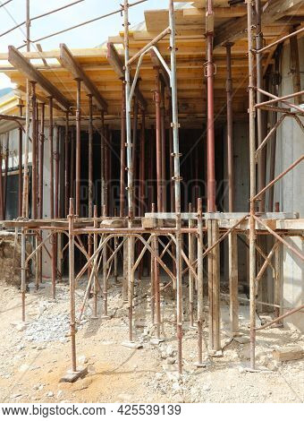 Many Scaffolding Of The Construction Site During The Renovation Of A Building With Energy-saving Mat
