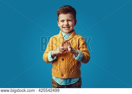 Little Cute Boy Kid In Stylish Yellow Cardigan Smiling Broadly And Looking At Camera Against Blue Ba