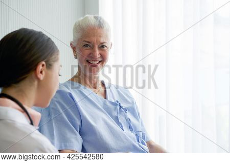 Elderly Female Patient Lying On The Bed In The Hospital Ward. The Young Doctor Examine The Symptom O