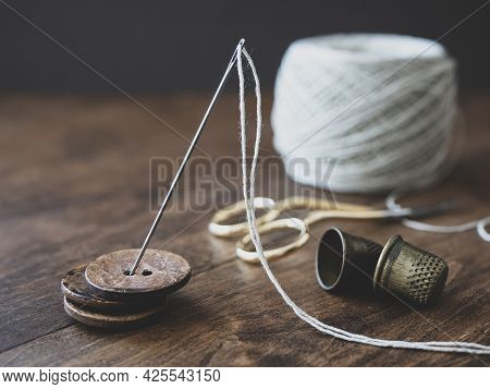 Pile Of Wooden Buttons, Needle, Old Thimbles, Scissors And A Cotton Thread Reel On The Table. Concep