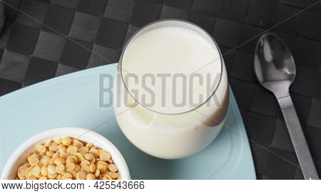 Soy Milk With No Sugar Added In A Glass On A Green Color Plastic Plate Mat.