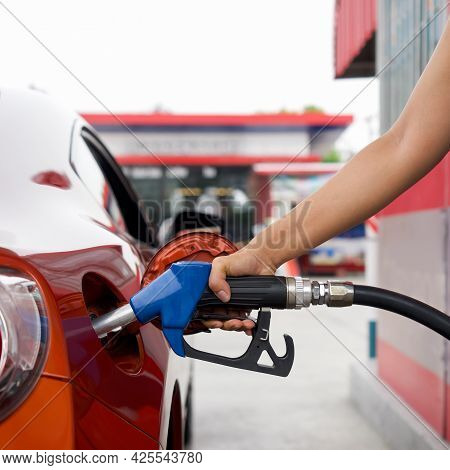 Gas Station Worker's Hand Holding Blue Benzene Gas Pump, Filling Up Red Sport Car Tank. Close Up