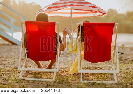 Man And Woman In Summer Clothes Laying At Red Beach Chairs On Sand Beach While Sunset. Focus Is At H