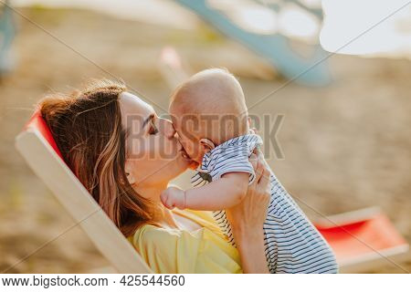 Young Pretty Mother In Yellow Summer Beach Dress Laying In Red Beach Chair Kissing Her Newborn Baby