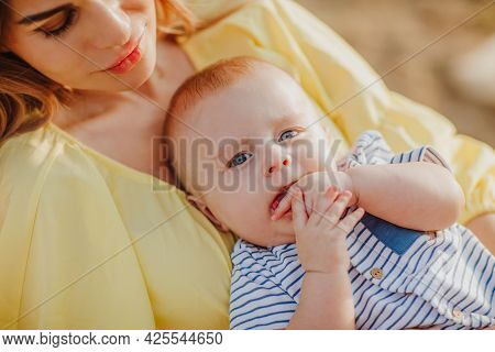Young Pretty Mother In Yellow Summer Beach Dress Laying In Red Beach Chair Holding Her Newborn Baby