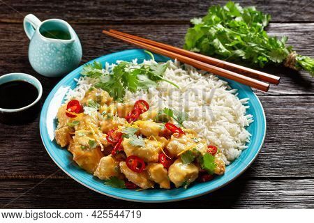 Mango Glazed Spicy Chicken Breast Chunks With Rice On A Blue Plate With Chopsticks, On A Dark Wooden
