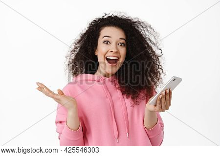 Surprised Natural Girl With Curly Hair, Holding Smartphone, React Amazed And Happy At Mobile Notific