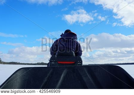 Man Rides A Snowmobile Rear View On A Winter Day