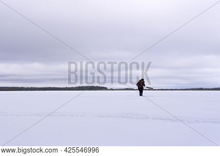 Man Drills Holes For Ice Fishing With An Electric Auger. Selective Focus